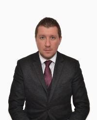 Мъж със сини очи позира, с черен костюм и лилава вратовръзка, позира официално