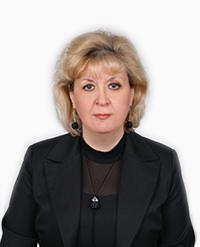 Жена на средна възраст с руса коса, в черни официални дрехи позира официално